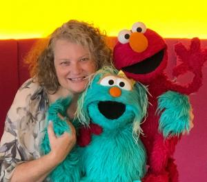 Tasha Weinstein poses with Sesame Street characters