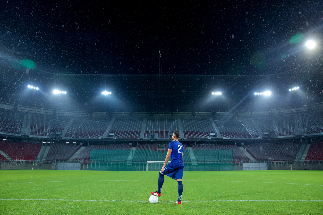Soccer player stands in the field of an empty stadium