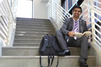 student sitting at stairs at college of education